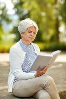 senior woman reading book at summer park