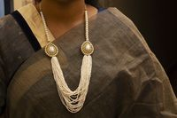 Women wearing multi layered small pearl necklace.