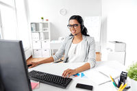businesswoman with headset and computer at office