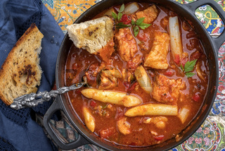 Traditional Creole cajun court bouillon with fish and gumbo chowder stew with white asparagus as top view in a pot