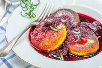 Curd fritters with cherry sauce with rosemary.