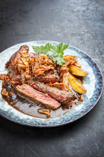 Traditional dry aged sliced roast beef with fried onion rings and potato chips as closeup on a plate with brown sauce with copy space