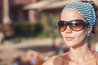 Beautiful and young girl in a striped orange swimsuit and sunglasses stands and Tans against the blurred backdrop of the beach resort. Closeup headshot with copyspace for your text
