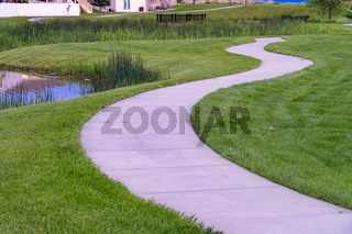 Close up of a pathway curving through a lush grassy terrain with a shiny pond