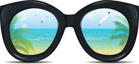 Summer sunglasses with a reflection of a tropical beach