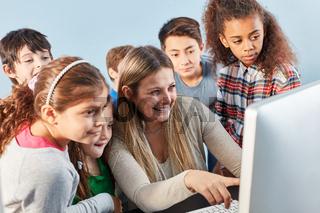 Lehrerin und Schüler Gruppe am Computer
