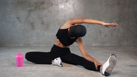 Happy healthy woman stretching at the gym
