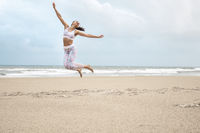 Young slim happy woman jumping on the sea beach sand