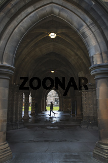 Student walking in the Glasgow University Cloisters
