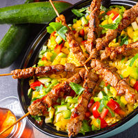 Lamb skewers with curry rice and different vegetables
