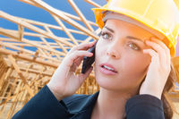 Concerned Female Contractor In Hard Hat Using Cell Phone At Construction Site