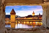 Luzern Kapelbrucke and riverfront architecture famous Swiss landmarks view through stone window