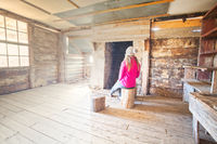 Woman sitting inside an old timber hut on log stools Snowy Mountains