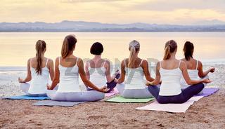 Back view women sitting in lotus pose meditating outdoors panoramic image