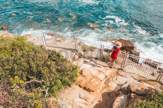 Woman at a fenced lookout over the ocean near Sydney