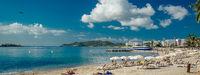 Panoramic image people sunbathing on Ibiza coast, Spain