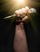 Vertical Microphone Clinched Firmly in Male Fist on a Black Background