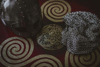 Costume Vikings, viking helmet with chain mail on a red shield with golden shapes of sun, weapons for war