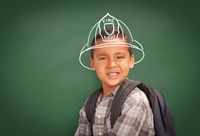Young Hispanic Student Boy Wearing Backpack Front Of Blackboard with Fireman Helmet Drawn In Chalk Over Head