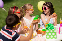 kids eating cupcakes on birthday party at summer