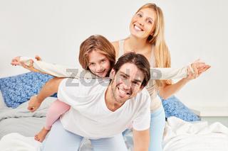Eltern albern mit ihrem Sohn im Bett herum