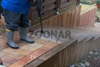 Woman works with a pressure washer