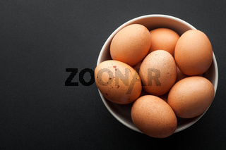 brown eggs in bowl isolated on dark background. top view