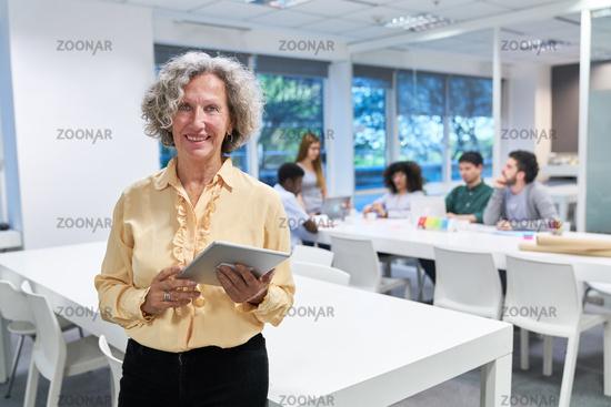 Dozentin mit Tablet vor einem Business Meeting
