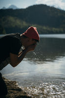 A man washes his hands on the shore of a forest lake