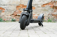 Electric kick scooter or e-scooter parked on pavement