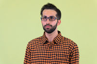 Face of young bearded Persian hipster man thinking