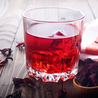 Closeup view at glass of tea with ice and spoon of dry hibiscus petals on wooden table background