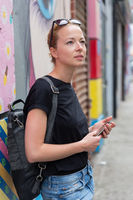 Female traveler using smart phone app guite on city break weekend trip to New York.