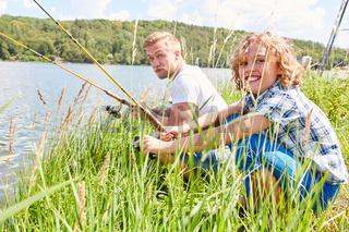 Vater und Sohn angeln zusammen am See