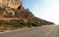 Evening sun shines on sharp rocks by the asphalt road - typical scenery on Karpasia peninsula in northern Cyprus