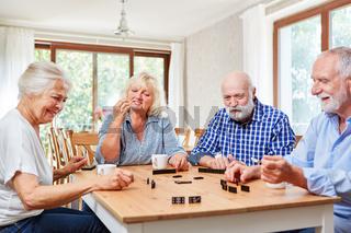 Gruppe Senioren beim Domino spielen
