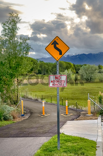 Winding Road Ahead and No Motorized Vehicles sign against nature background