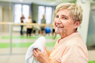Erschöpfte Senior Frau in einer Pause im Fitnesscenter