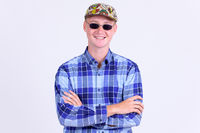 Happy young hipster man smiling with arms crossed