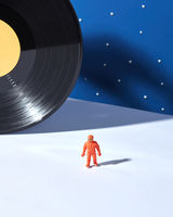 Astronaut in outer space agaimst of black vinyl record and duotone blue white background