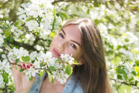 Woman near blooming apple tree