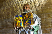 priest of the rock-hewn church Mikael Mellehayzengi showing the book Miracles of Maria,Ethiopia