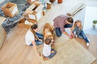 Eltern und Kinder messen einen Teppich aus