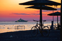Beach and parasols on colorful sunset with large yacht view