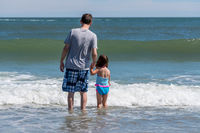 Rear view of father and young daughter facing the ocean waves
