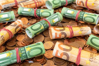 Pile of cents with Euro banknote rolls