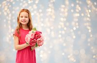 happy red haired girl with flowers over lights