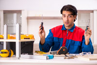 Young contractor repairing furniture at home