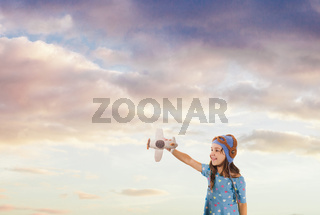 Cute girl dreaming of summer holidays with a knitted toy airplane