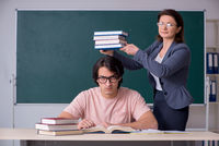 Old female teacher and male student in the classroom